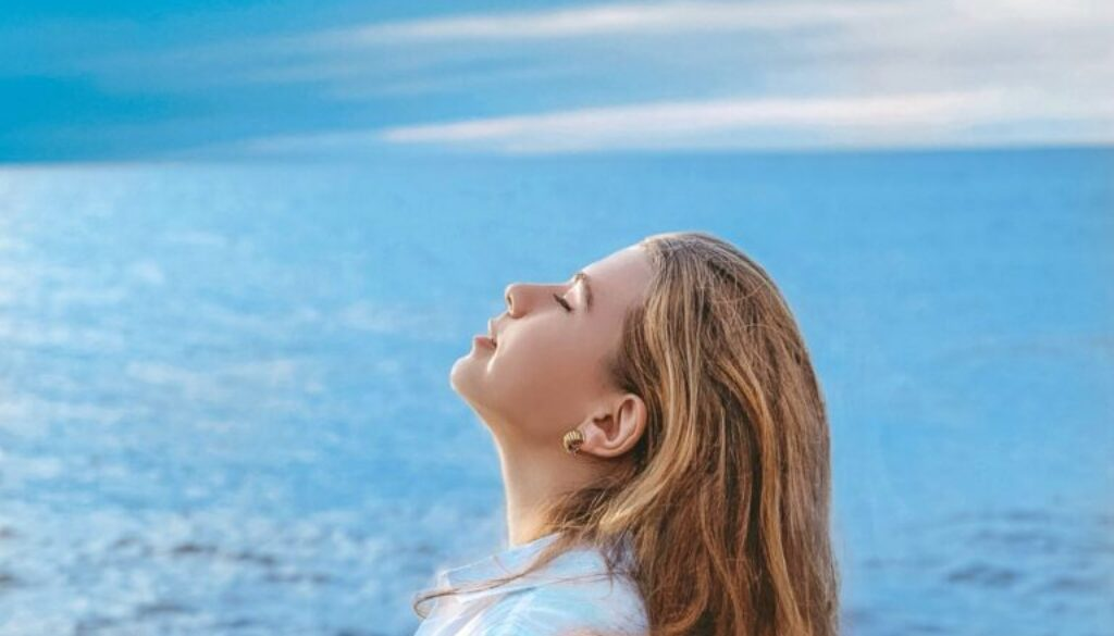 preteen girl on the beach shown in profile against the ocean and a clear blue sky
