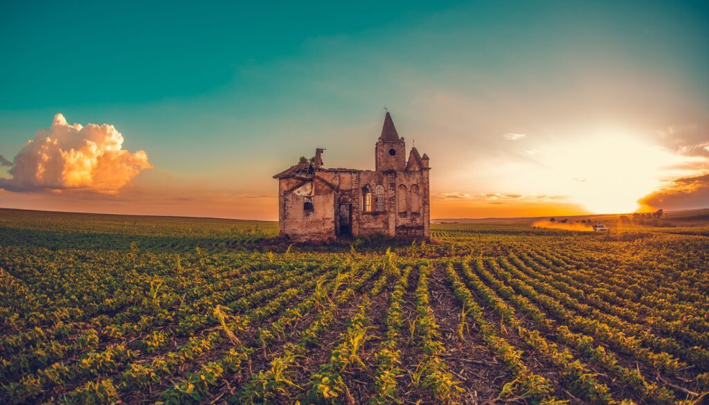 quirky looking abandoned house in the middle of a field with sunset in the background