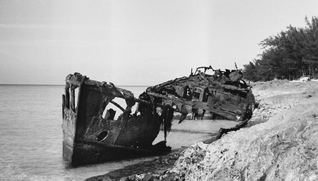 the ravaged hull of an ancient ship wrecked upon a sandy shore