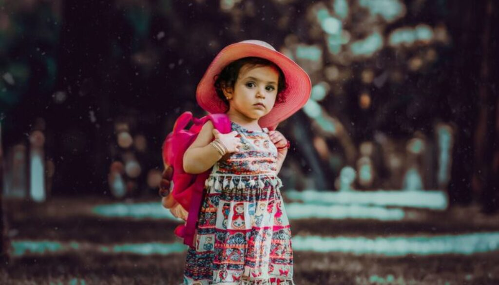 three year old little girl standing outside with a pink hat and pink backpack