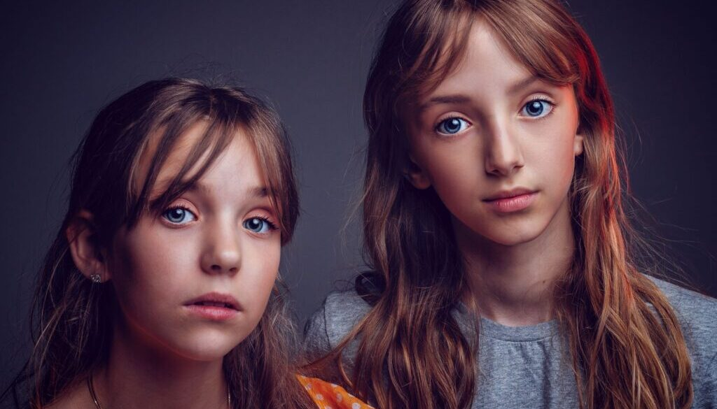 two pretty preteen sisters with big eyes photographed against a black background