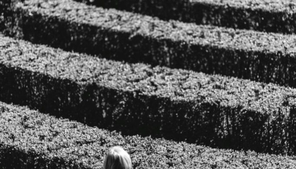 woman standing outside in a hedgerow maze