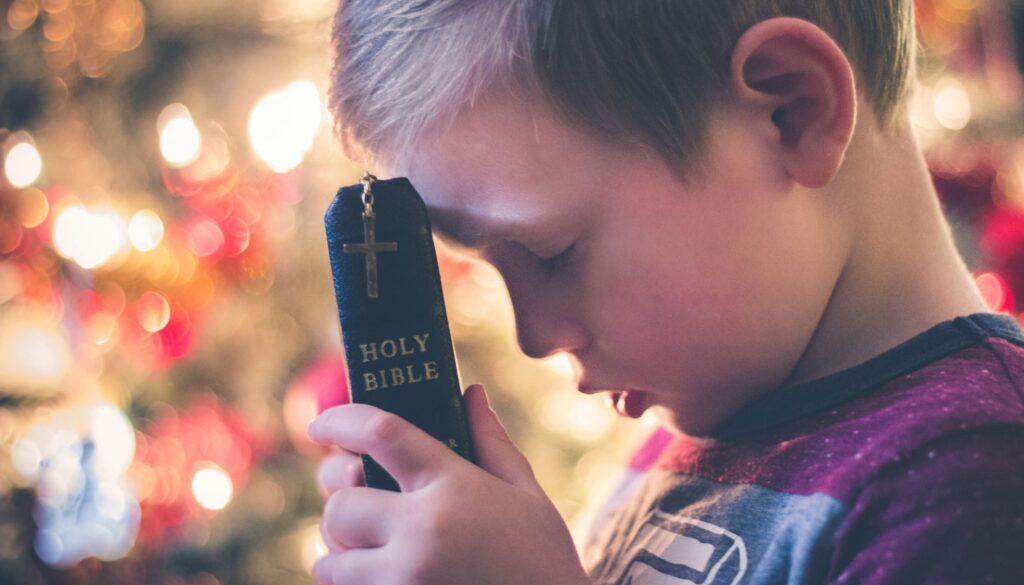 Little boy holding a Bible in front of a lighted Christmas tree