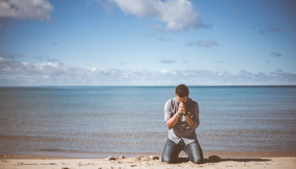 man praying on his knees in the sand next to a large lake or ocean