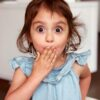 Surprised little girl with hand over her mouth and wide eyes