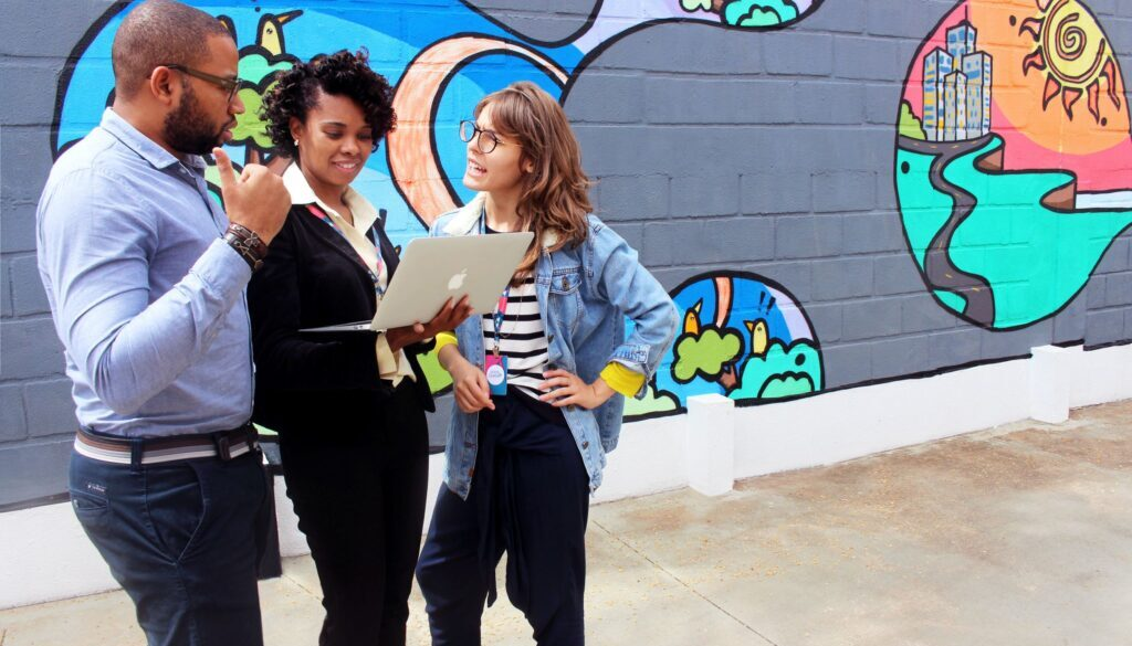 three young adults standing outside looking at a laptop computer with a graffiti wall in the background