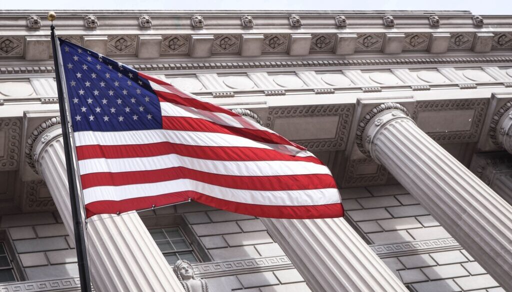 american flag flying in front of a large white columned federal building