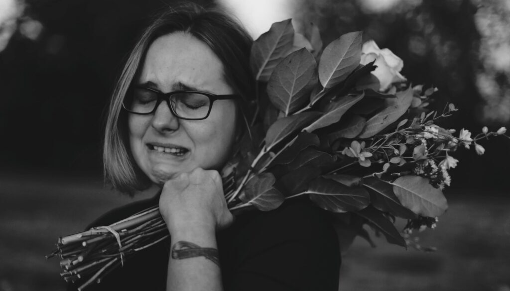 grayscale photo of a woman in black crying while carrying a bouquet of flowers on her shoulder outside on a dreary day