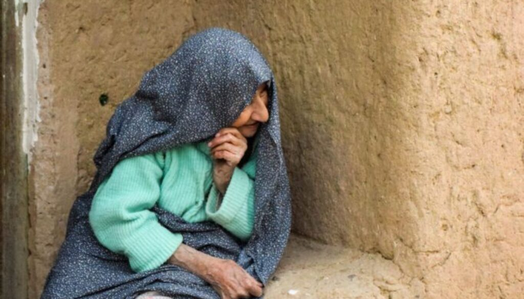 middle eastern elderly woman sitting down in an ancient town looking around the corner