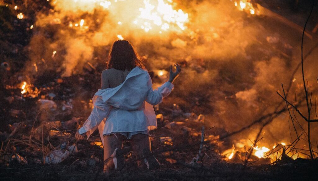 woman in white in front of a burning forest fire