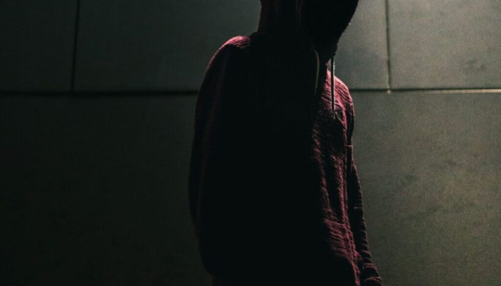 a mysterious figure darkly lit against a concrete wall background