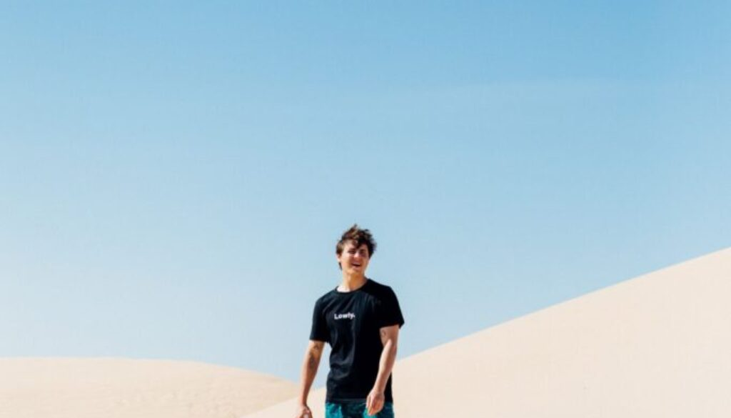 young man standing in the middle of a desert on a white sand dune