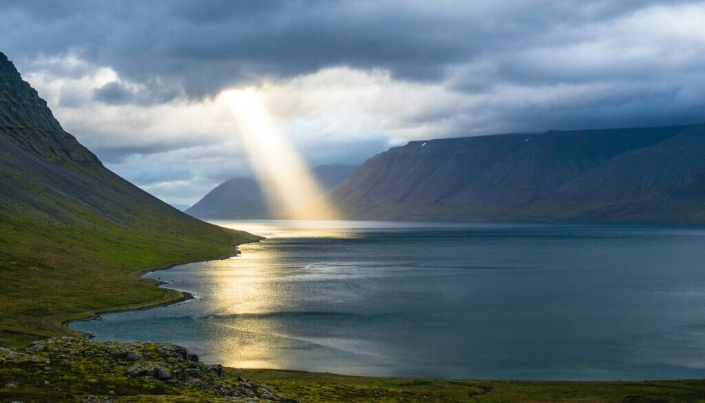 a ray of light breaking through the clouds to illuminate the water of a pristine bay