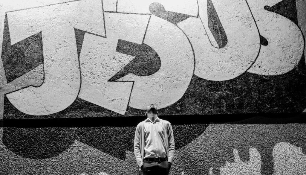 black and white photo of a young man standing outside looking up with the name JESUS written in grafitti behind him