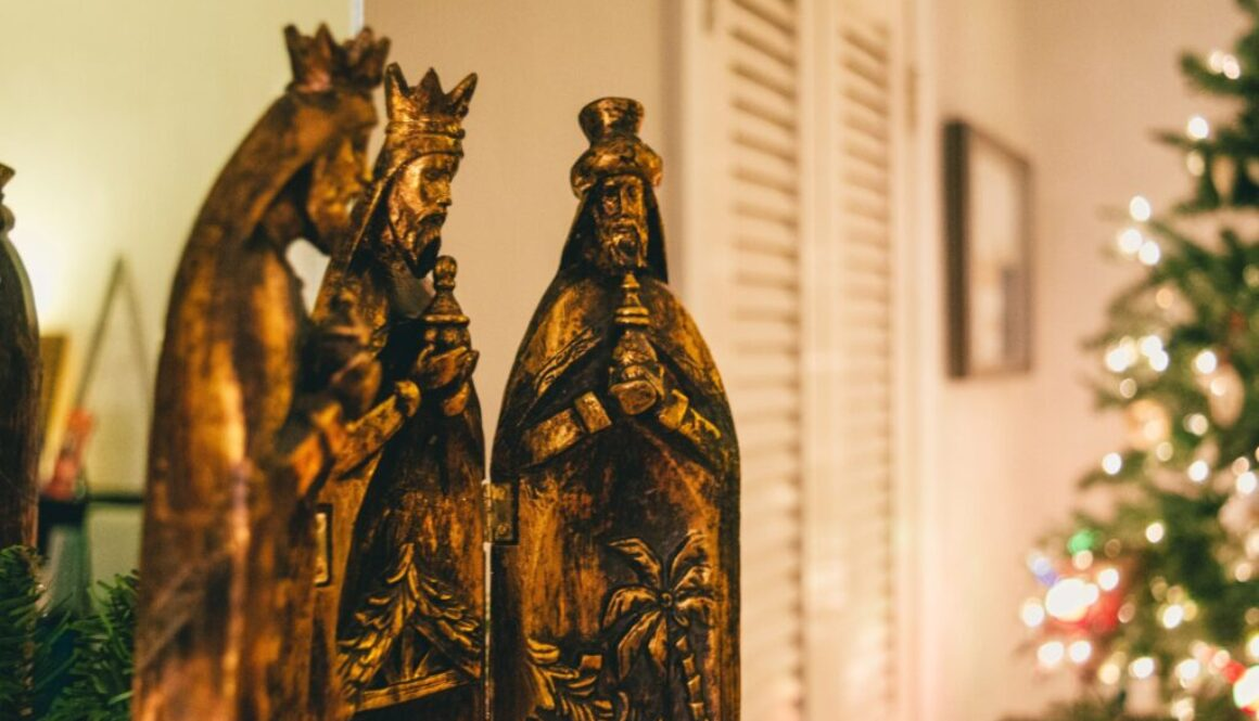 bronze statues of the three wise men pictured in a modern living room with a Christmas tree in the background