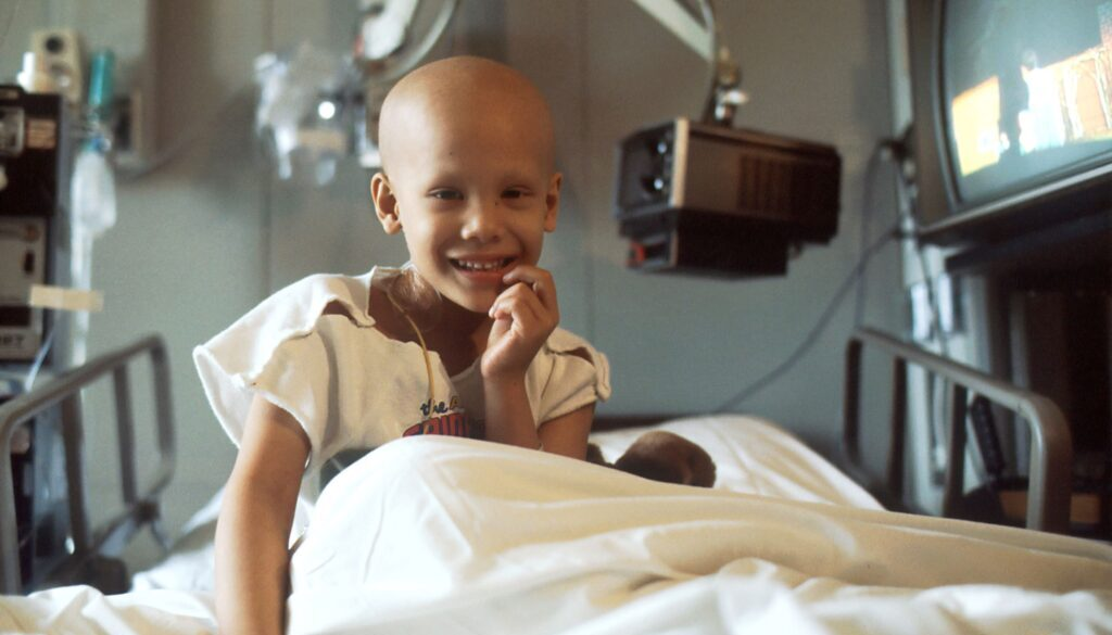 cute bald child in a cancer hospital bed smiling and hopeful