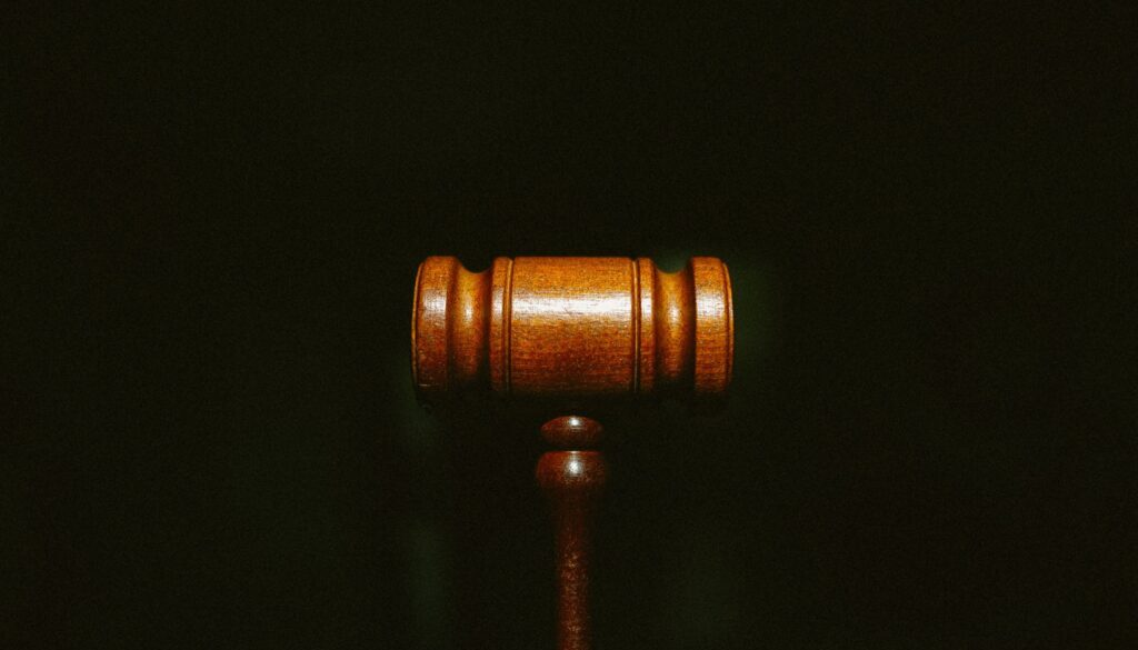 high def picture of a wooden gavel illuminated against a black background