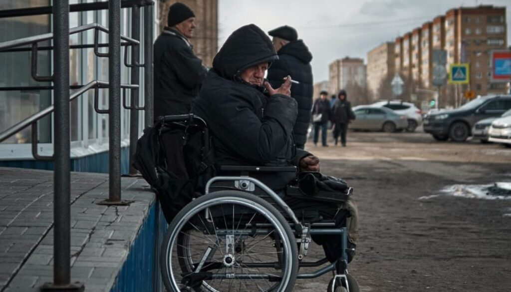 man sitting in a wheelchair outside a soup kitchen on skid row