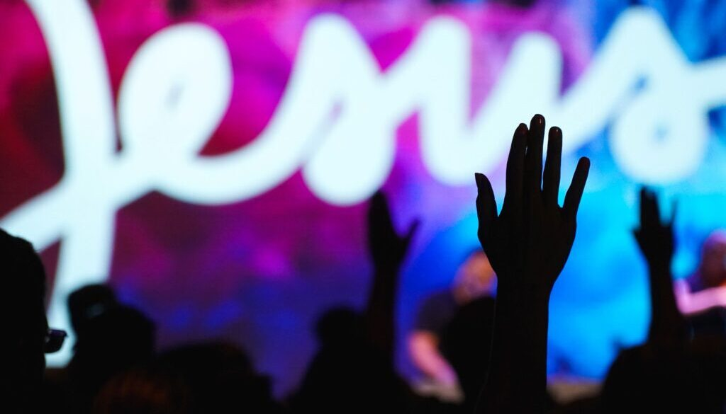 silhouette of uplifted hands of worshiper against a background of the word Jesus in neon
