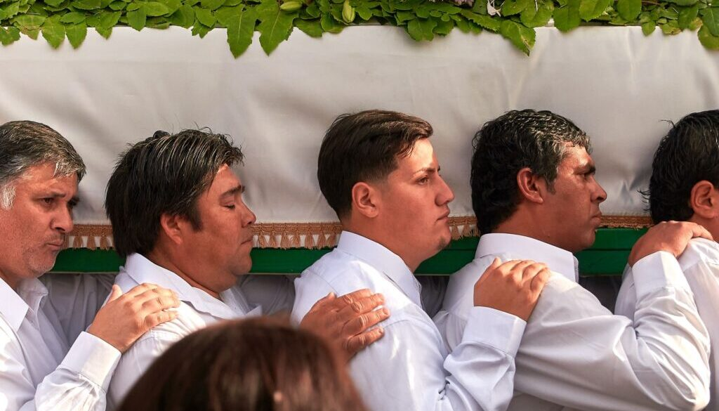 men in white carrying a coffin