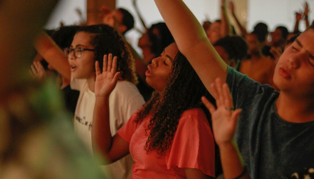 diverse group of worshipers with hands raised and eyes closed