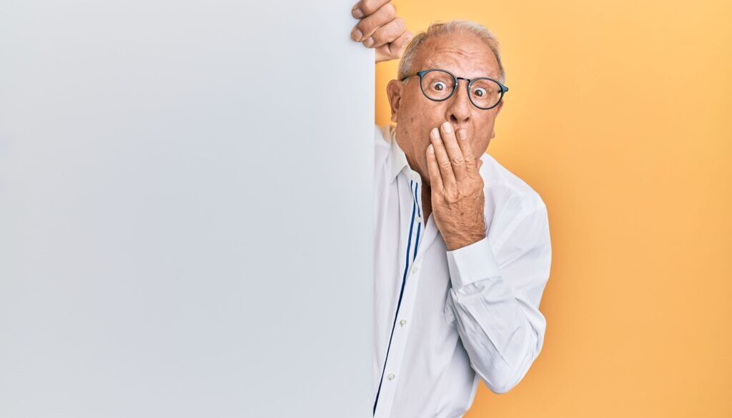 elderly man peering around a corner with a surprised look on his face