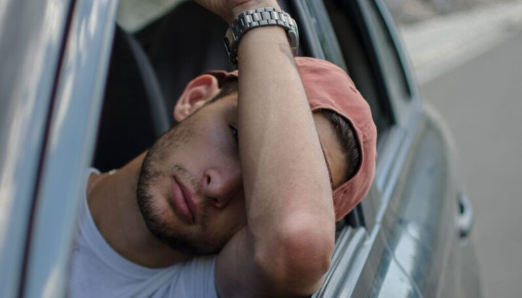 flustered young man stuck in traffic with car window open and his head resting on his elbos