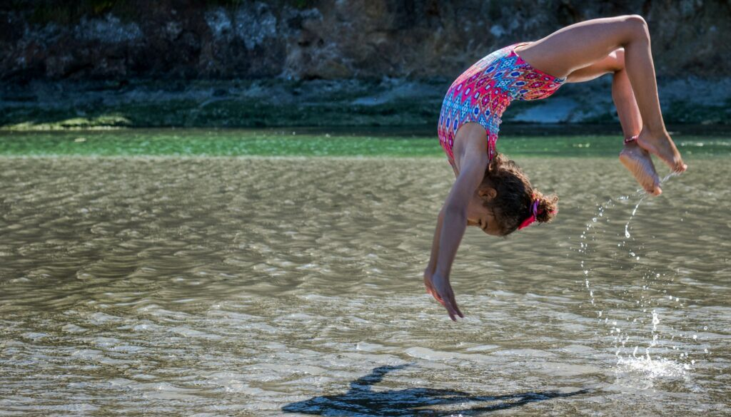 little girl in the sunshine doing a backflip into a lake