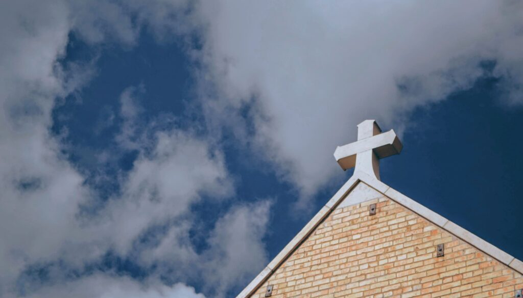 picture of a church with a white cross on the peak of its roof set against a bright cloudy blue sky