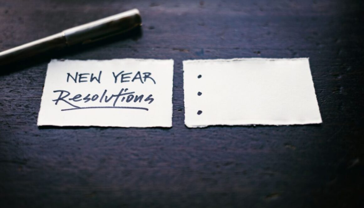 post it notes lying on a desk containing the words new year's resolutions written in felt tip pen