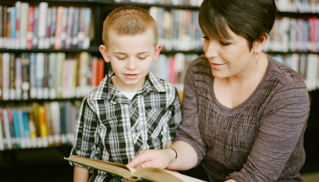 teacher reading to a little boy in a library
