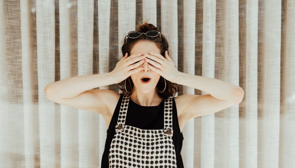 woman in an apron covering her eyes in scandal and surprise