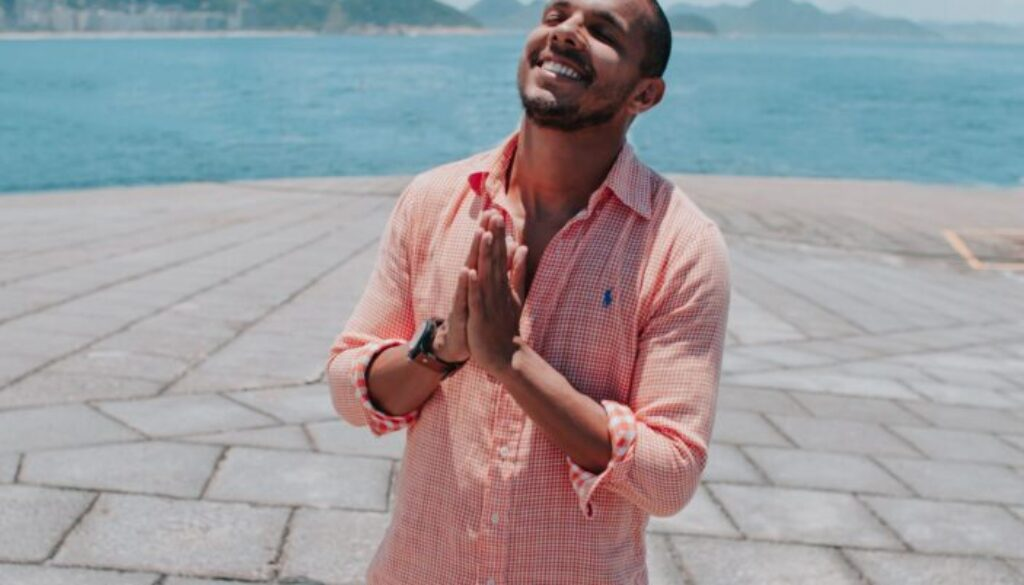 young man in a pink shirt standing on a paved patio looking up and smiling with clasped hands with the blue sky and tropical sea in the background