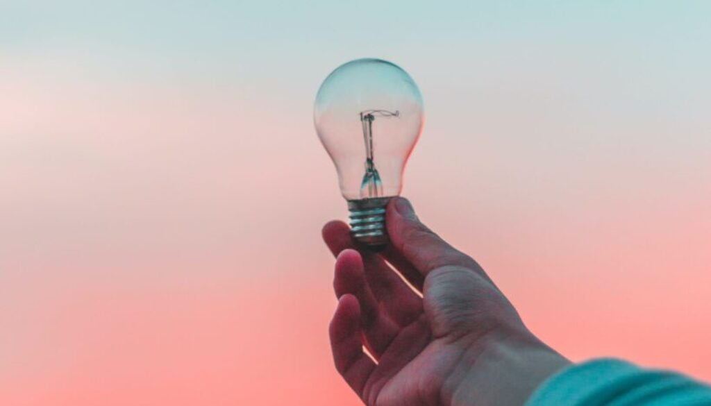 young man's hand holding a light bulb against a pink and blue morning sky