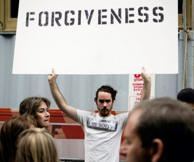 young man holding up a sign saying forgiveness