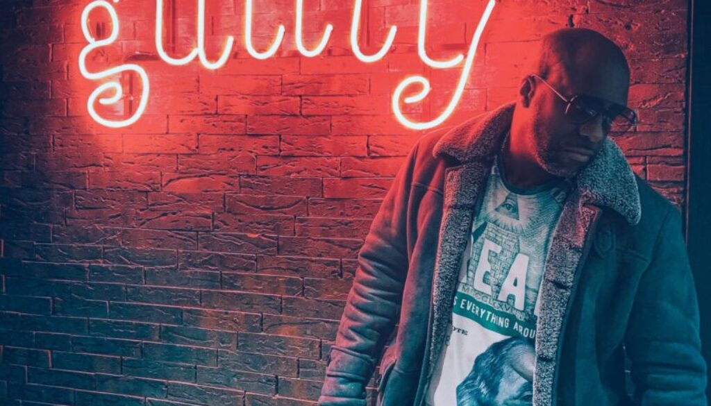 young man in an urban setting standing in front of a brick wall with the word guilty written behind him in red neon