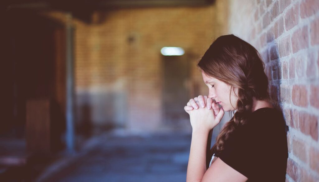 young woman standing against a brick wall praying in desperation