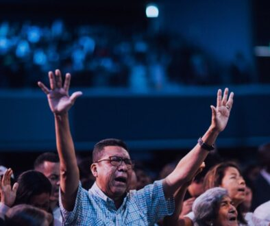 a church congregation raising their hands in worship
