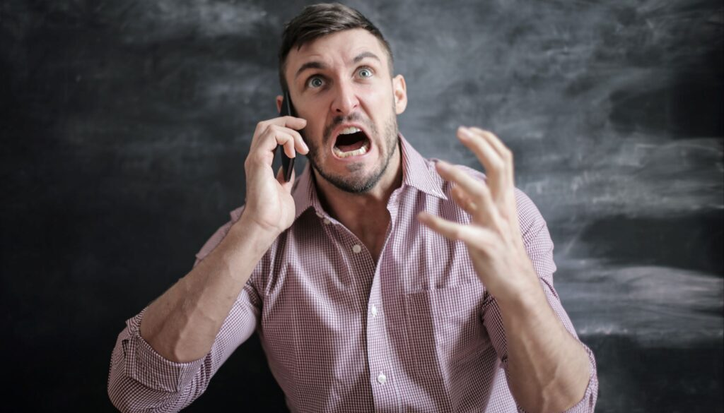 angry man speaking on the phone while standing in front of a dark gray background