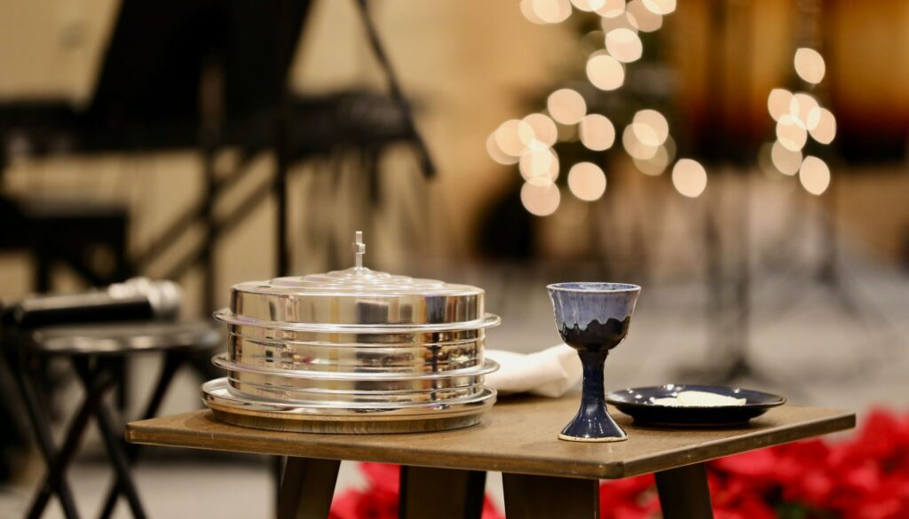 communion set with wine and bread with church stage candles and musical instruments in the background