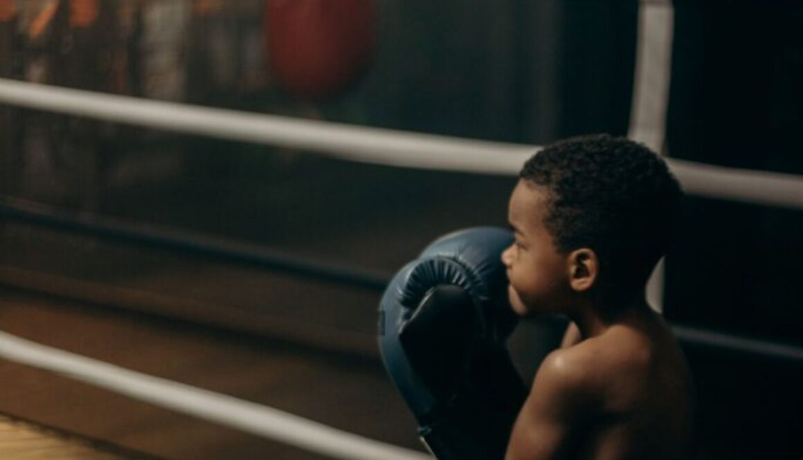 cute little boy with oversized gloves in a boxing ring