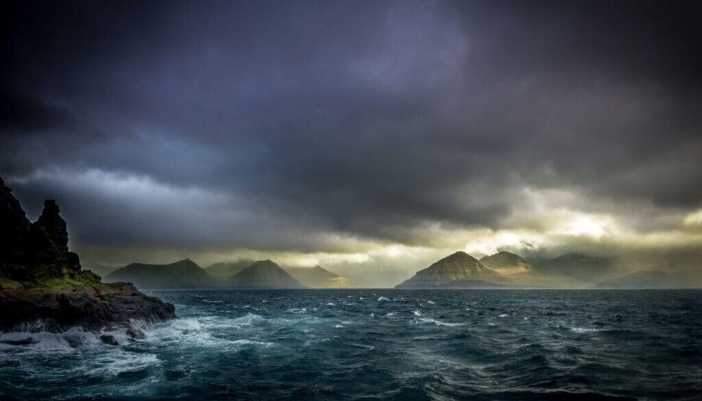 dark stormy lake with rocky seashore and mountains in the background