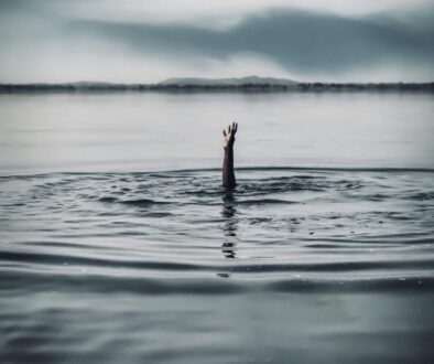 drowning man's hand reaching out of the water