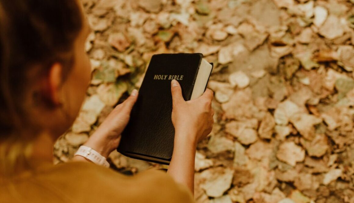 photo looking down at a woman holding a Bible in a setting of autumn leaves