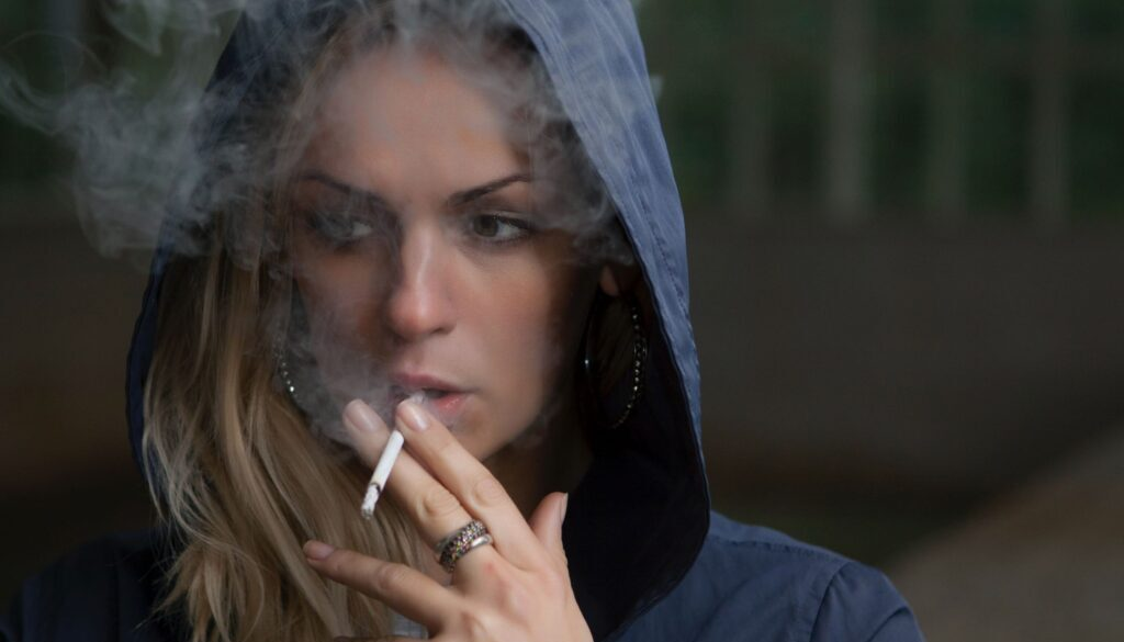 pretty young woman with cigarette and hoodie