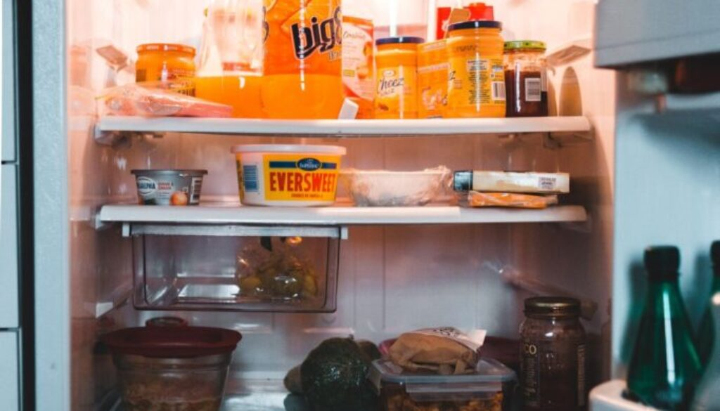 refrigerator with door open showing a variety of foods drinks and leftovers