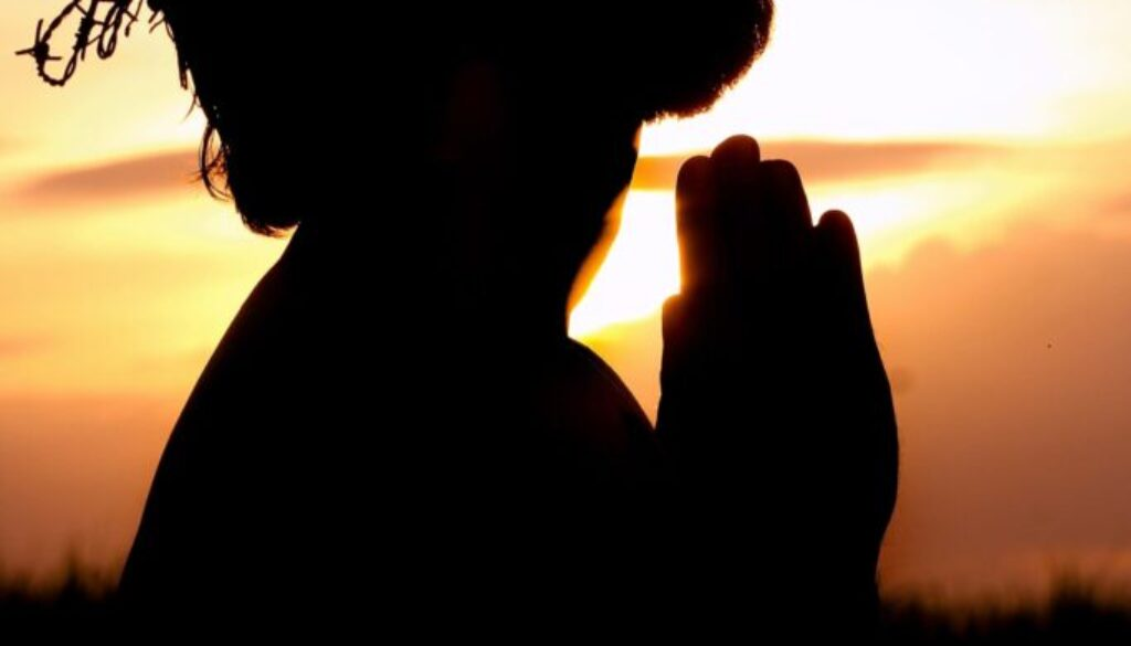 silhouette of Jesus praying against a red sky