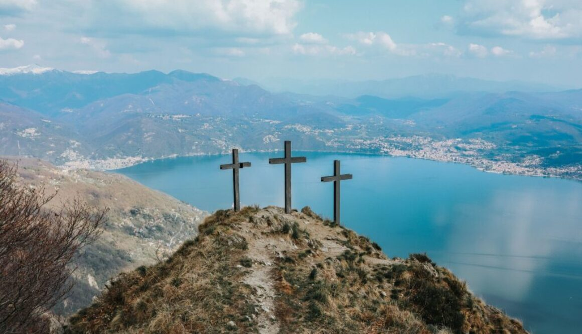 three crosses on a mountaintop overlooking a beautiful bay and city harbor