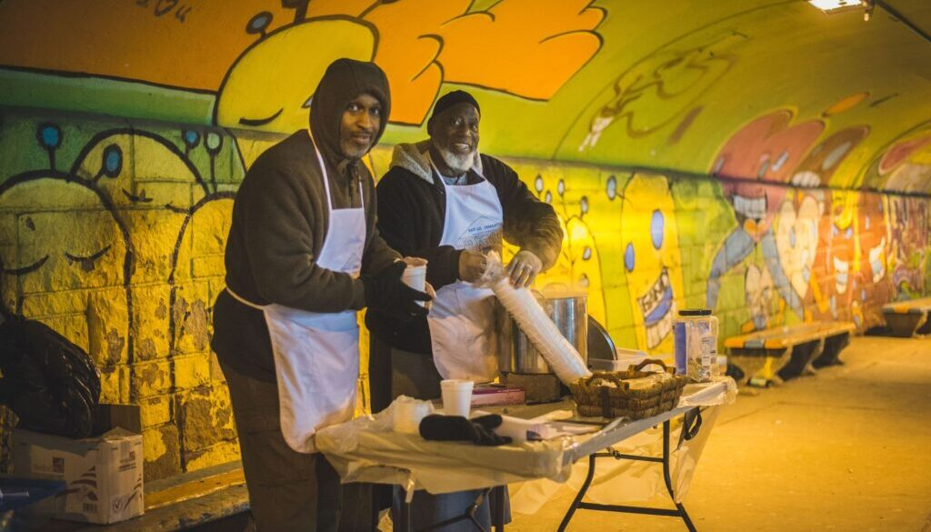 two happy men in a graffiti covered subway tunnel serving food to hungry people