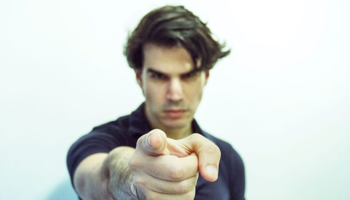 young man pointing his finger straight at the camera in an accusatory fashion